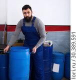 Купить «Worker transporting barrels in motorcycle workshop», фото № 30389591, снято 19 апреля 2019 г. (c) Яков Филимонов / Фотобанк Лори