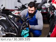 Купить «diligent man worker working at restoring motorbike in workshop», фото № 30389595, снято 19 апреля 2019 г. (c) Яков Филимонов / Фотобанк Лори