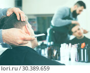 Купить «Male hairdresser accurately cutting beard», фото № 30389659, снято 27 января 2017 г. (c) Яков Филимонов / Фотобанк Лори