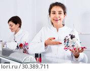 Купить «Female manicurist showing lacquer color schemes», фото № 30389711, снято 2 февраля 2017 г. (c) Яков Филимонов / Фотобанк Лори
