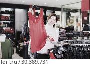 Купить «Woman chooses red blouse», фото № 30389731, снято 7 февраля 2017 г. (c) Яков Филимонов / Фотобанк Лори