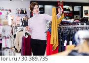 Купить «Woman choosing colorful blouse», фото № 30389735, снято 7 февраля 2017 г. (c) Яков Филимонов / Фотобанк Лори