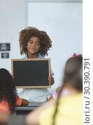 Купить «African ethnicity schoolboy holding a slate and looking at camera in classroom», фото № 30390791, снято 17 ноября 2018 г. (c) Wavebreak Media / Фотобанк Лори