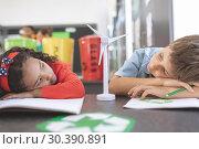 Купить «Two tired school kids observing a windmill mockup between them», фото № 30390891, снято 17 ноября 2018 г. (c) Wavebreak Media / Фотобанк Лори