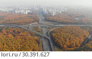 Купить «Top view of the multi-level road junction in Moscow from above, car traffic and many cars, the concept of transportation», видеоролик № 30391627, снято 24 марта 2019 г. (c) Mikhail Starodubov / Фотобанк Лори
