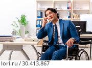 Купить «Male employee in wheelchair working at the office», фото № 30413867, снято 4 декабря 2018 г. (c) Elnur / Фотобанк Лори