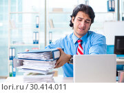 Купить «Handsome businessman unhappy with excessive work in the office», фото № 30414011, снято 19 ноября 2018 г. (c) Elnur / Фотобанк Лори