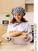 Купить «Young female baker working in kitchen», фото № 30414507, снято 2 ноября 2018 г. (c) Elnur / Фотобанк Лори