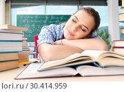 Купить «Female student with many books sitting in the classroom», фото № 30414959, снято 19 ноября 2018 г. (c) Elnur / Фотобанк Лори