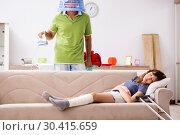 Купить «Husband helping leg injured wife in housework», фото № 30415659, снято 4 октября 2018 г. (c) Elnur / Фотобанк Лори