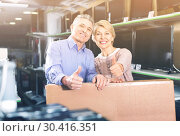 Купить «Mature couple are happy with choice and purchased consumer electronics», фото № 30416351, снято 21 ноября 2019 г. (c) Яков Филимонов / Фотобанк Лори