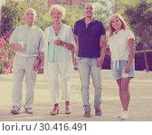 Купить «Smiling family of four walking with plastic cups», фото № 30416491, снято 24 августа 2017 г. (c) Яков Филимонов / Фотобанк Лори
