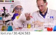 Купить «Chemistry teacher and schoolgirl conducting experiments with chemical reagents in a chemical laboratory», видеоролик № 30424583, снято 27 марта 2019 г. (c) Алексей Кузнецов / Фотобанк Лори
