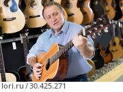 Купить «Man is playing on acoustic guitar», фото № 30425271, снято 18 сентября 2017 г. (c) Яков Филимонов / Фотобанк Лори