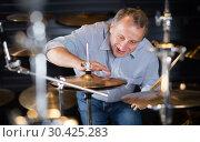 Купить «smiling musician is choosing modern drum kit», фото № 30425283, снято 18 сентября 2017 г. (c) Яков Филимонов / Фотобанк Лори