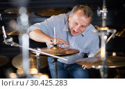 smiling musician is choosing modern drum kit. Стоковое фото, фотограф Яков Филимонов / Фотобанк Лори