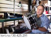 Купить «Adult man is choosing drum kit in music store.», фото № 30425291, снято 18 сентября 2017 г. (c) Яков Филимонов / Фотобанк Лори