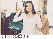 Купить «Cute girl customer with packs delighted from purchases», фото № 30425519, снято 17 января 2018 г. (c) Яков Филимонов / Фотобанк Лори