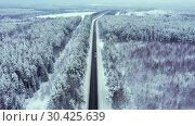 Купить «Winter road with ice on the asphalt, trees under snow during the winter frost», видеоролик № 30425639, снято 17 марта 2019 г. (c) Mikhail Starodubov / Фотобанк Лори