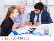 Купить «Managers are writing financial reports and discussing with mature boss», фото № 30434735, снято 27 июня 2017 г. (c) Яков Филимонов / Фотобанк Лори