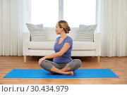Купить «woman doing twist in lotus pose at home», фото № 30434979, снято 13 ноября 2015 г. (c) Syda Productions / Фотобанк Лори