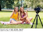 Купить «teenage bloggers recording video by camera in park», фото № 30435367, снято 19 июля 2018 г. (c) Syda Productions / Фотобанк Лори