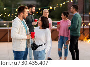 Купить «friends with drinks in party cups at rooftop», фото № 30435407, снято 2 сентября 2018 г. (c) Syda Productions / Фотобанк Лори