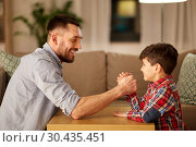 happy father and little son arm wrestling at home. Стоковое фото, фотограф Syda Productions / Фотобанк Лори