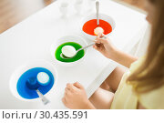 Купить «girl coloring easter eggs by liquid dye at home», фото № 30435591, снято 25 июля 2018 г. (c) Syda Productions / Фотобанк Лори