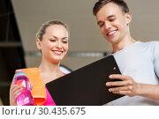 Купить «woman and personal trainer with clipboard in gym», фото № 30435675, снято 29 июня 2014 г. (c) Syda Productions / Фотобанк Лори
