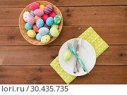 Купить «easter eggs in basket, plates, cutlery and flowers», фото № 30435735, снято 15 марта 2018 г. (c) Syda Productions / Фотобанк Лори