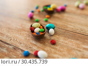 Купить «chocolate egg and candy drops on wooden table», фото № 30435739, снято 15 марта 2018 г. (c) Syda Productions / Фотобанк Лори