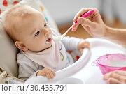 Купить «father feeding baby sitting in highchair at home», фото № 30435791, снято 25 августа 2018 г. (c) Syda Productions / Фотобанк Лори