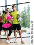 Купить «sportive couple with water bottles and bags in gym», фото № 30435943, снято 29 июня 2014 г. (c) Syda Productions / Фотобанк Лори