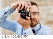 Купить «photographer or hipster with film camera outdoors», фото № 30435951, снято 30 мая 2015 г. (c) Syda Productions / Фотобанк Лори