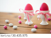 Купить «easter eggs in holders and candy drops on table», фото № 30435975, снято 15 марта 2018 г. (c) Syda Productions / Фотобанк Лори