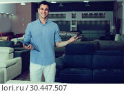 Купить «Seller male is demonstrating prices on sofas», фото № 30447507, снято 19 июня 2017 г. (c) Яков Филимонов / Фотобанк Лори