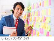 Купить «Young handsome employee with many conflicting priorities», фото № 30451699, снято 16 октября 2018 г. (c) Elnur / Фотобанк Лори
