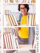Купить «Male student preparing for exams at library», фото № 30452611, снято 14 декабря 2018 г. (c) Elnur / Фотобанк Лори