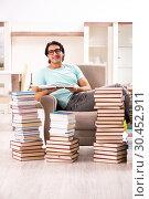 Купить «Male student with many books at home», фото № 30452911, снято 6 декабря 2018 г. (c) Elnur / Фотобанк Лори