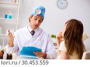 Young woman visting male doctor otolaryngologist. Стоковое фото, фотограф Elnur / Фотобанк Лори