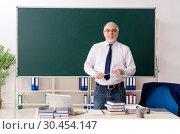 Купить «Aged male teacher in front of chalkboard», фото № 30454147, снято 20 декабря 2018 г. (c) Elnur / Фотобанк Лори