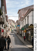 One of the typical narrow streets in the city center. People walk on the sidewalks lined with tile patterns, Ponta Delgada, Azores (2012 год). Редакционное фото, фотограф Юлия Бабкина / Фотобанк Лори