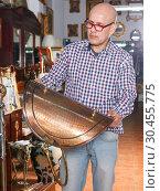 Купить «man pensively looking at antique goods», фото № 30455775, снято 15 мая 2018 г. (c) Яков Филимонов / Фотобанк Лори