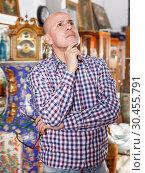 Купить «Intelligent male carefully examining antiques», фото № 30455791, снято 15 мая 2018 г. (c) Яков Филимонов / Фотобанк Лори