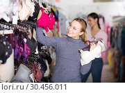 Happy woman holding different brassiere in hands. Стоковое фото, фотограф Яков Филимонов / Фотобанк Лори