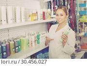 Купить «Smiling girl seller advising on pet shampoo», фото № 30456027, снято 22 апреля 2019 г. (c) Яков Филимонов / Фотобанк Лори