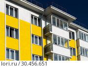 Купить «Fragment of brightly colored apartment building with balconies», фото № 30456651, снято 4 июня 2018 г. (c) Володина Ольга / Фотобанк Лори