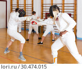 Купить «Joyful group practicing fencing techniques», фото № 30474015, снято 30 мая 2018 г. (c) Яков Филимонов / Фотобанк Лори