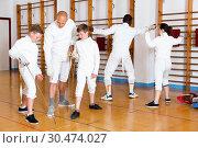 Купить «Focused boys fencers attentively listening to professional fencing coach in gym», фото № 30474027, снято 30 мая 2018 г. (c) Яков Филимонов / Фотобанк Лори
